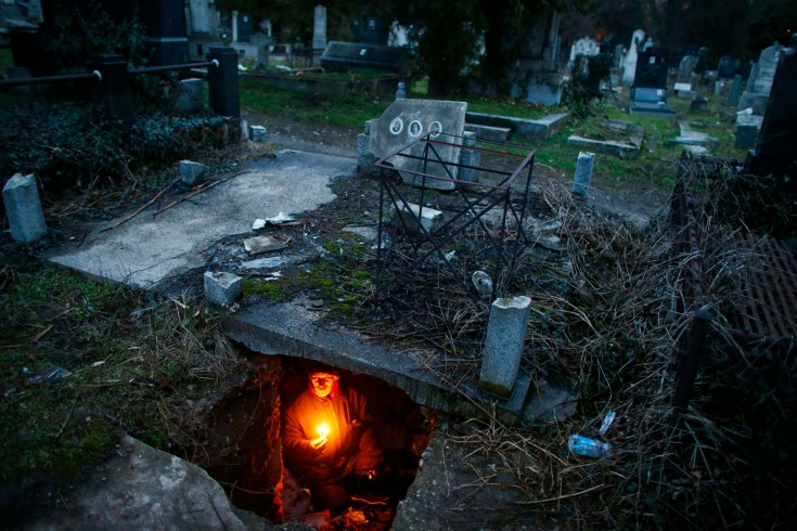 Bratislav Stojanovic, a homeless man, hold candles as sits in a tomb where he lives in southern Serbian town of Nis