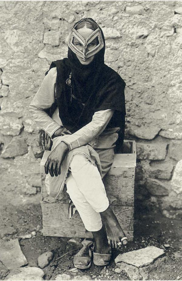 A woman wearing a traditional face mask in Muscat, Oman. 1905. Photo by A.R. Fernandez