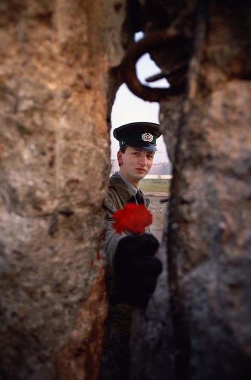East German soldier passing a flower through the Berlin Wall in 1989